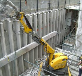 Operator Using Brokk Remote Controlled Machinery To Crunch Concrete